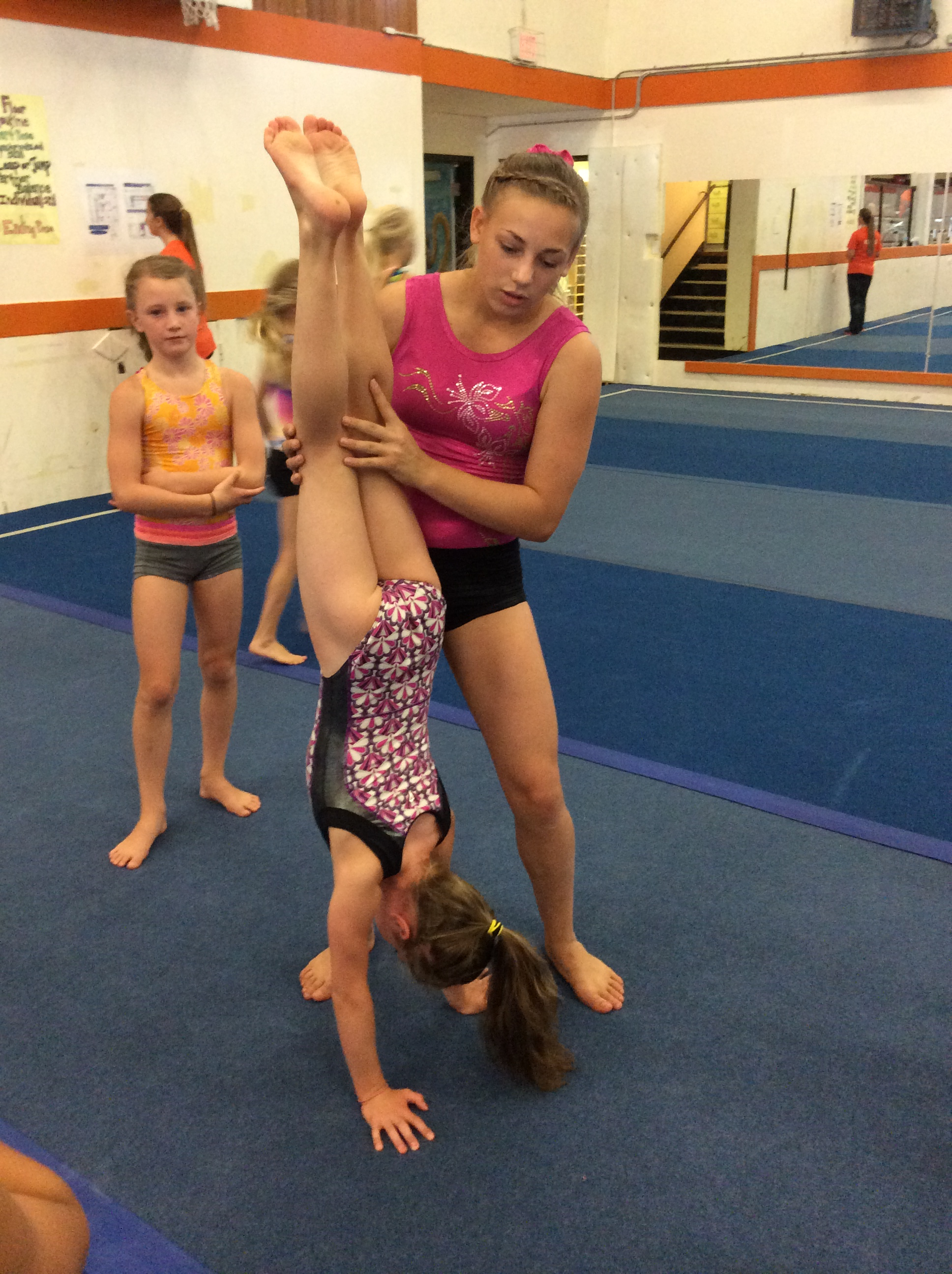 gymnastic junior Darby, a junior gymnastics instructor from Vancouver Island, helps local  gymnast Hillary with a handstand at Powell River Gymnastics Centre earlier  this ...